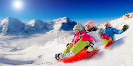 Winter fun, snow, family sledding at winter time