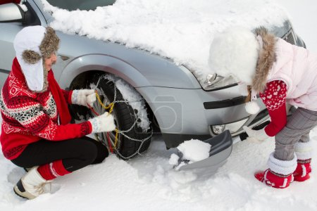 Winter, travel - woman putting snow chains onto tyre of car