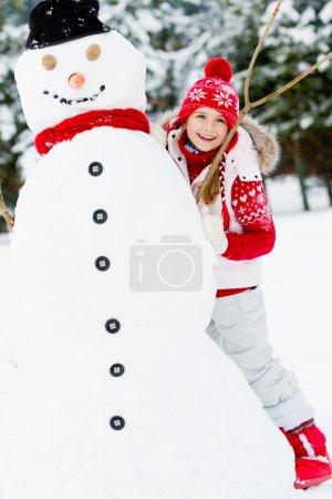 Winter, snowman - lovely girl has a fun in snow