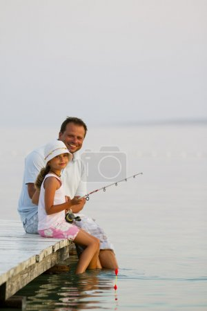 Fishing - girl with father fishing on the pier