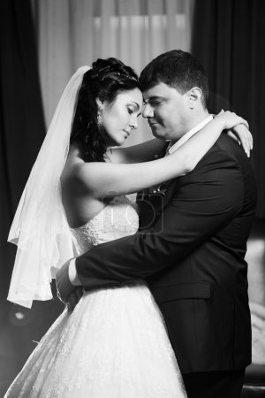 Bride and groom dancing in the restaurant. Black and white photo
