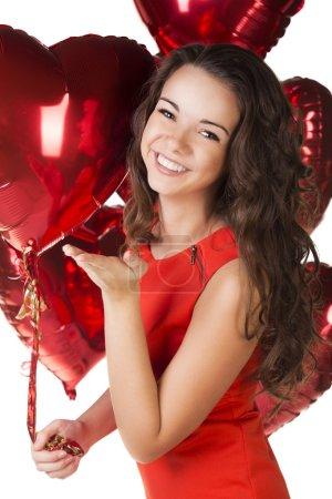 Foto de Día de San Valentín. mujer sonriendo sosteniendo el globo rojo en forma de corazón. - Imagen libre de derechos