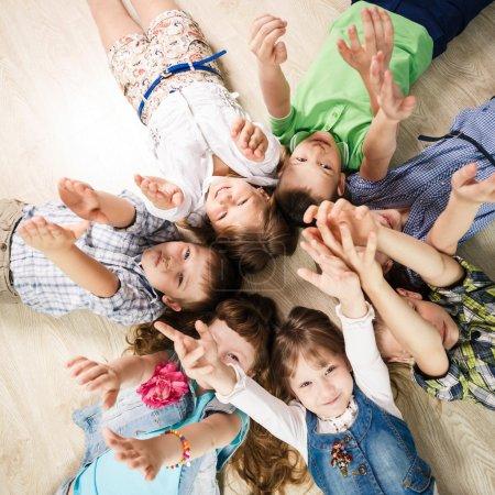 Photo pour Groupe d'enfants heureux couché en forme d'étoile sur le sol avec les mains levées - image libre de droit