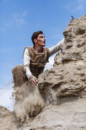 Photo pour L'homme dans le désert grimpe - image libre de droit
