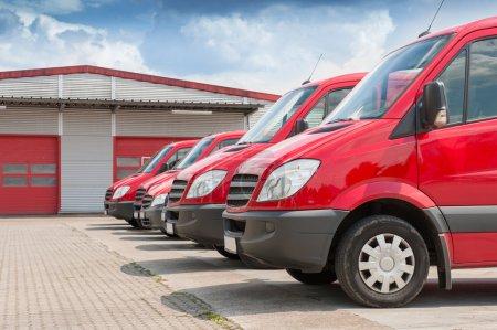 Photo pour Rangée de voitures de livraison et de service rouges devant une usine et une usine de distribution d'entrepôt - image libre de droit