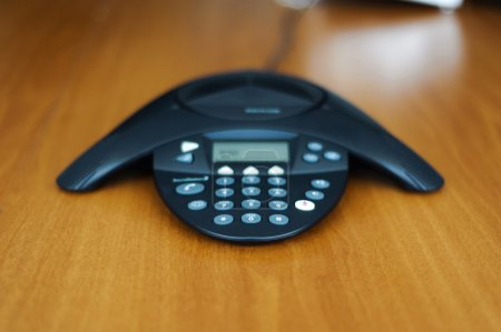 Conference business phone in meeting room on a wooden background