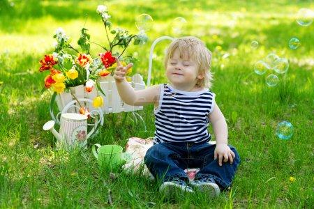 Photo pour Adorable petit garçon assis sur l'herbe verte les yeux fermés entourés de fleurs et de bulles de savon - image libre de droit