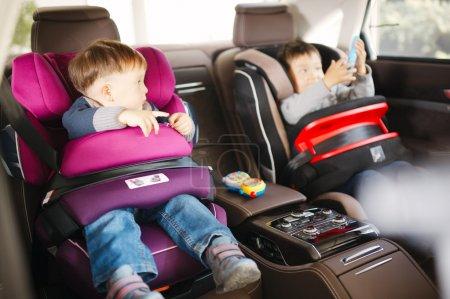 Photo pour Siège d'auto de bébé luxe de sécurité avec des enfants heureux - image libre de droit