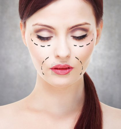 Beautiful young woman with perforation lines on her face before plastic surgery.