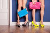 Dvě dívky nosí vysoké podpatky, které čekají na dveře