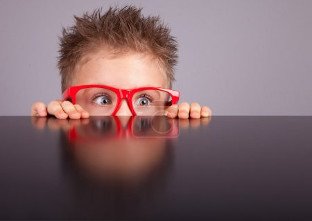 Photo for Five years old little cute boy hiding behind a table - Royalty Free Image