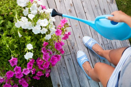 Woman watering flowers on a patio deck