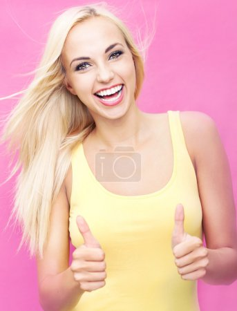Beautiful young woman with an amazing smile showing thumbs up