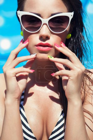 Woman wearing sunglasses by the swimming pool