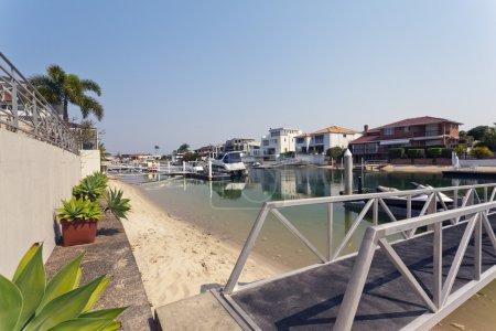 lake and pier behind modern australian mansion