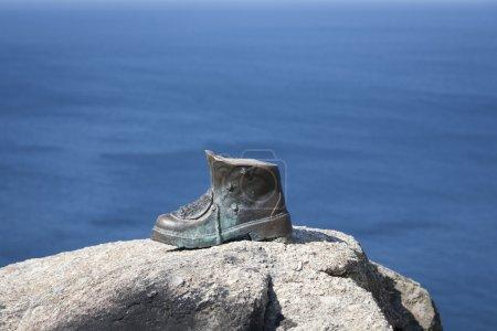 Photo pour La botte de bronze du cap Finisterre, en Espagne, marque la fin du pèlerinage et les pèlerins qui ont terminé avec succès le parcours du Camino de Santiago. Ici, ils brûlent leurs bottes et leurs vêtements . - image libre de droit