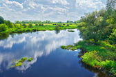 Spring landscape with Narew river and clouds on the sky