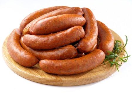 Sausages on round kitchen cutting board