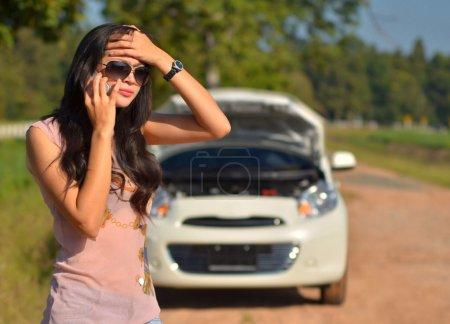 Photo pour Une femme appelle à l'aide après que sa voiture est tombé en panne - image libre de droit
