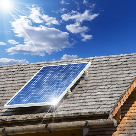 Foto de Techo viejo con tejas de madera y panel solar con reflejo del cielo azul - Imagen libre de derechos