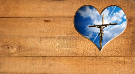 Photo for Wooden wall with a hole in the shape of heart with Jesus crucified and blue sky with cloud - Royalty Free Image