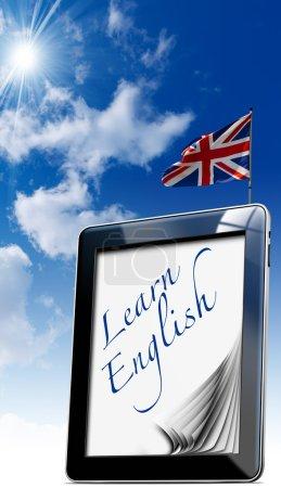 """Photo pour Tablette noire avec des pages et le mot """"apprendre l'anglais"""" sur l'écran et drapeau britannique sur un sk bleu - image libre de droit"""