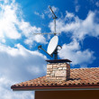 Satellite dish and TV antennas on the house roof w...