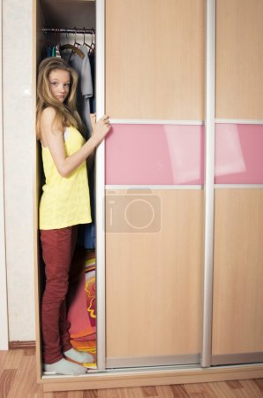 Photo for Teenage girl hiding in wardrobe at home - Royalty Free Image