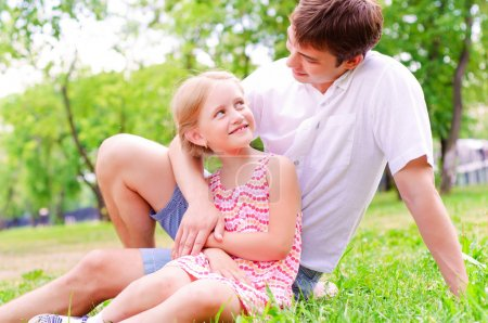 Photo for Father and daughter sitting together on the grass, and spend time with family - Royalty Free Image