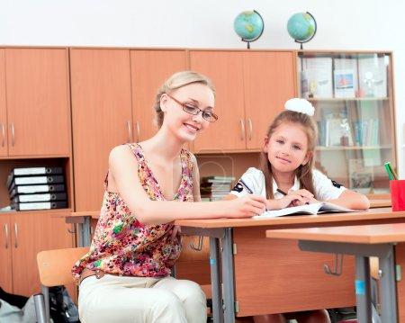 Teacher sitting near pupil