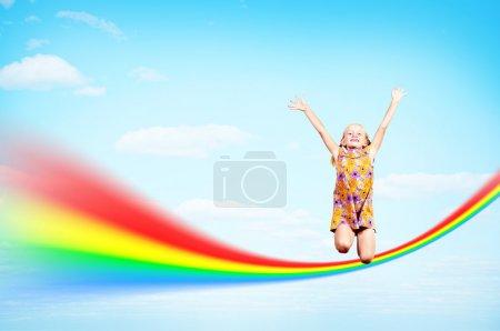 Photo pour Fille sautant sur les nuages et un arc-en-ciel, collage, endroit pour le texte - image libre de droit