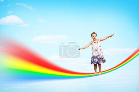 Foto de Niña saltando sobre las nubes y un arco iris, collage, lugar para el texto - Imagen libre de derechos