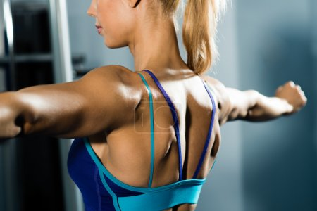 Photo for Female athlete straining back muscles and arms, do sport in the fitness club - Royalty Free Image
