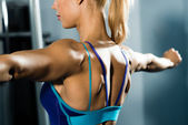 Female athlete straining back muscles and arms