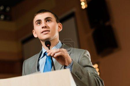 Photo pour Portrait d'un homme d'affaires tenant le micro sur la Conférence, parle dans le micro et se penche sur la chambre - image libre de droit