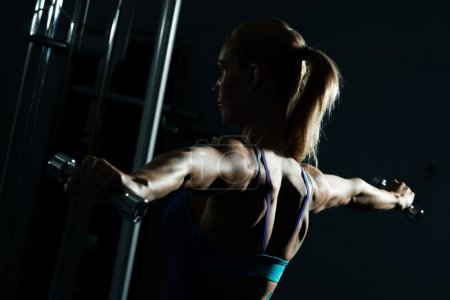 Photo for Female athlete dumbbell, exercise in the fitness club - Royalty Free Image