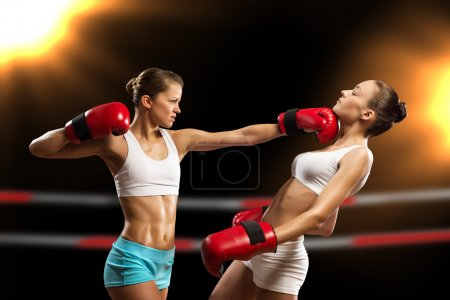 Photo for Aggressive boxing woman, hits an opponent in the head - Royalty Free Image
