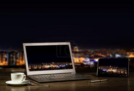 Photo pour Ordinateur portable et tablette, homme d'affaires au travail dans la ville de nuit - image libre de droit