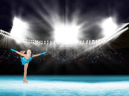 Photo pour Effectue une jeune patineur sur la glace dans la lumière de l'arrière-plan d'éclairage - image libre de droit