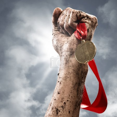Photo for Hand holding a winner's medal, success in competitions - Royalty Free Image