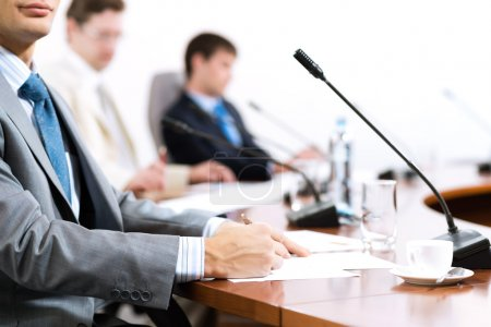 Photo for Businessman writing on paper notes, to communicate with colleagues in the background - Royalty Free Image