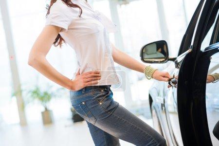 Photo pour Femme ouvre la porte à une nouvelle voiture, l'inspection des wagons dans la salle d'exposition - image libre de droit