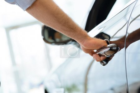 Photo for Man opens the door to a new car, car inspection in the showroom - Royalty Free Image