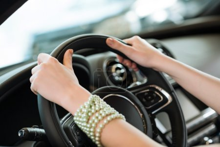 woman's hands holding on to the wheel of a new car