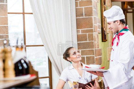 Photo for Chef brings a dish pretty woman in a restaurant, a pleasant time forwarding - Royalty Free Image