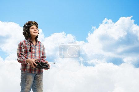 Photo for Little boy in a helmet pilot keeps remote control, in the background sky and clouds - Royalty Free Image