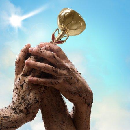 Photo pour Main tenant une tasse du vainqueur, l'autre main est attirée vers lui - image libre de droit