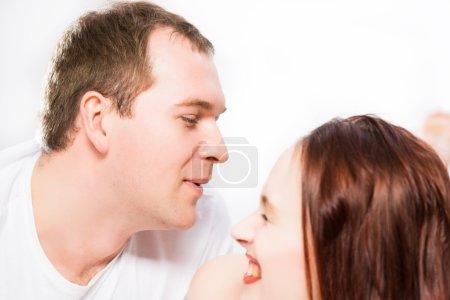 Photo pour Jeune homme et femme couchés ensemble au lit, souriants et heureux - image libre de droit