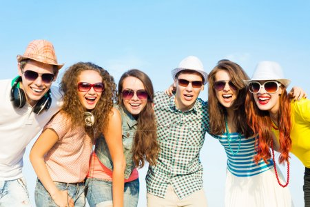 Photo for Group of young people wearing sunglasses and hats hugging and standing in a row, spending time with friends - Royalty Free Image