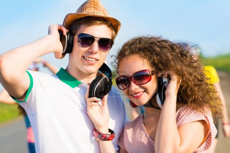Photo for Young couple standing on the road, having fun with friends - Royalty Free Image